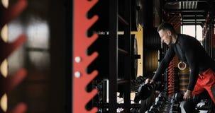 El hombre de la aptitud ejecuta ejercicio del bíceps con pesa de gimnasia Atleta con la pesa de gimnasia que dobla los músculos e almacen de video