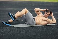 El hombre de la aptitud que el hacer se sienta sube en la elaboración del estadio Varón muscular que ejercita los abdominals, al  Foto de archivo libre de regalías
