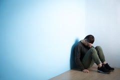 El hombre de la depresión se sienta en piso imagen de archivo libre de regalías