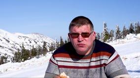 El hombre de la estación de esquí come comida campestre en la estación de esquí en invierno en primer soleado del tiempo almacen de metraje de vídeo