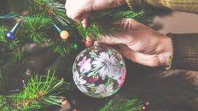 El hombre de la mano adorna el juguete hermoso del árbol de navidad Fotografía de archivo