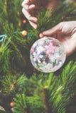 El hombre de la mano adorna el juguete hermoso del árbol de navidad Imagen de archivo libre de regalías