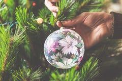 El hombre de la mano adorna el juguete hermoso del árbol de navidad Foto de archivo
