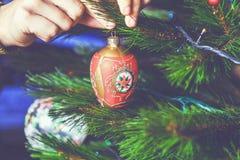 El hombre de la mano adorna el juguete rojo hermoso del árbol de navidad Imagen de archivo