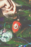 El hombre de la mano adorna el juguete rojo hermoso del árbol de navidad Imagenes de archivo
