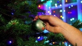 El hombre de la mano que adorna en el árbol de navidad con resplandor de la Navidad se enciende metrajes