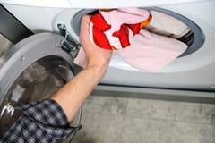 El hombre de la mano toma cosas con la lavadora imagen de archivo