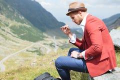 El hombre de la moda de los jóvenes fuma en naturaleza Imagen de archivo
