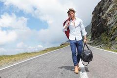 El hombre de la moda de los jóvenes viene abajo del camino Imagen de archivo libre de regalías
