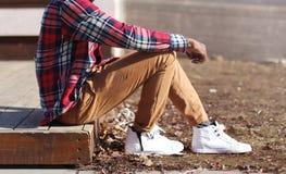 El hombre de la moda en una camisa roja y zapatillas de deporte casuales de la tela escocesa se sienta Fotos de archivo