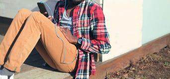 El hombre de la moda escucha la música en el smartphone que se sienta en ciudad Fotos de archivo libres de regalías