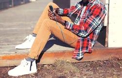 El hombre de la moda escucha la música usando el smartphone que se sienta en la ciudad Imagen de archivo