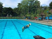 El hombre de la natación salta en el agua de la piscina Imagen del concepto del deporte acuático Imágenes de archivo libres de regalías