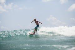 El hombre de la persona que practica surf que practica surf en ondas salpica activamente Imagenes de archivo