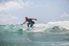El hombre de la persona que practica surf que practica surf en ondas salpica activamente Imágenes de archivo libres de regalías