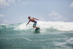 El hombre de la persona que practica surf que practica surf en ondas salpica activamente Fotografía de archivo libre de regalías