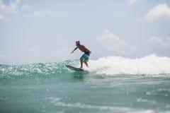 El hombre de la persona que practica surf que practica surf en ondas salpica activamente Imagen de archivo libre de regalías