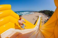 El hombre de la playa salta la diapositiva de apogeo de los paseos Imágenes de archivo libres de regalías