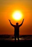 El hombre de la silueta encendido sostiene el sol Fotografía de archivo libre de regalías