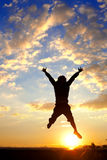 El hombre de la silueta salta sobre puesta del sol Foto de archivo