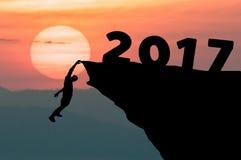 El hombre de la silueta sube en el acantilado al ajuste de la meta de la Feliz Año Nuevo 2017 de la palabra con puesta del sol en Foto de archivo