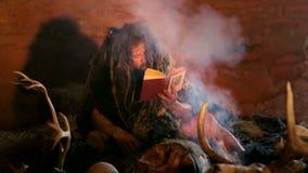 El hombre de las cavernas prehistórico lee el libro almacen de video