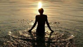 El hombre de los Arty aumenta el agua de río en manos y la lanza para arriba en Sunny Path Sunset almacen de video