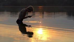 El hombre de los Arty aumenta el agua de río en palmas y la deja bajar en la puesta del sol almacen de metraje de vídeo