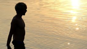 El hombre de los Arty aumenta el agua de río en palmas y la lanza para arriba en Sunny Path Sunset metrajes