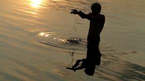 El hombre de los Arty mira el agua de río de los aumentos en puñados baja abajo en corrientes en la puesta del sol metrajes