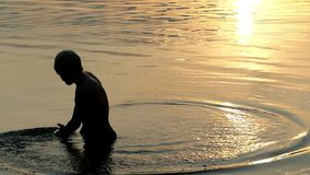 El hombre de los Arty mueve el agua de río con su palma en Sunny Path Sunset almacen de video