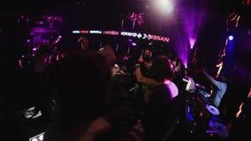 El hombre de Mc se realiza en etapa con los muchachos Gente que baila en partido en club nocturno aclamación almacen de metraje de vídeo