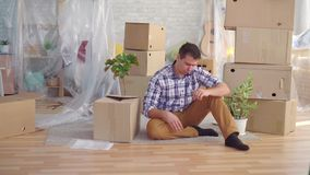 El hombre de mediana edad cansado y trastornado del retrato con los vidrios entre las cajas a moverse, lee los documentos para el almacen de video