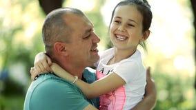 El hombre de mediana edad detiene a una hija en sus brazos, la besa en la mejilla Sonríen y ríen almacen de metraje de vídeo