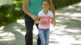 El hombre de mediana edad que la pluma lanza para arriba a su hija en el parque de la ciudad a cámara lenta entonces él se va, la metrajes