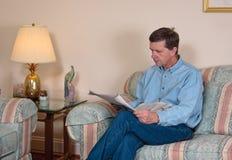 El hombre de mediana edad se relaja en el sofá imagen de archivo libre de regalías