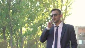 El hombre de mirada confiado y peligroso vestido en negro va en la calle con el teléfono almacen de metraje de vídeo