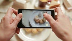 El hombre de moda en un restaurante hace la foto de la comida con la cámara del teléfono móvil metrajes