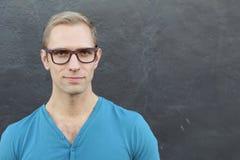 El hombre de moda fresco joven con los vidrios que sonreía con los brazos cruzó sobre fondo azul con el espacio de la copia Fotos de archivo