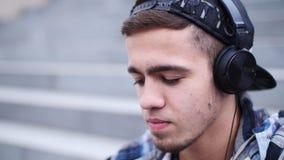 El hombre de moda joven escucha la música en el smartphone que se sienta en los pasos al aire libre almacen de metraje de vídeo
