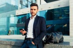 El hombre de moda joven hermoso en un traje de negocios elegante y gafas de sol está mecanografiando un mensaje imágenes de archivo libres de regalías