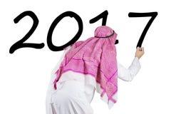 El hombre de negocios árabe escribe el número 2017 con el marcador Fotografía de archivo