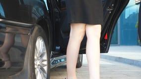 El hombre de negocios abre la puerta para la mujer joven hermosa El hombre destapa la puerta del automóvil para el pasajero femen metrajes