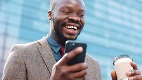 El hombre de negocios acertado afroamericano feliz consigue grandes noticias en smartphone Él se coloca cerca de un centro de la  almacen de video