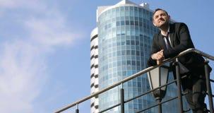 El hombre de negocios acertado considera hacia fuera la vista del horizonte de la ciudad el día Un hombre encima de un edificio q almacen de metraje de vídeo