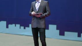 El hombre de negocios acertado en un traje trabaja con la tableta metrajes