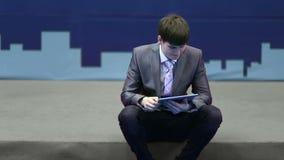 El hombre de negocios acertado en un traje trabaja con la tableta almacen de metraje de vídeo