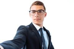 El hombre de negocios acertado en vidrios y traje, toma un selfie con foto de archivo libre de regalías