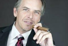El hombre de negocios acertado fuma el cigarro Imagenes de archivo