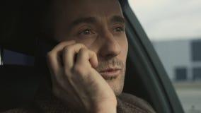 El hombre de negocios acertado habla por el teléfono que se sienta en primer del coche almacen de metraje de vídeo